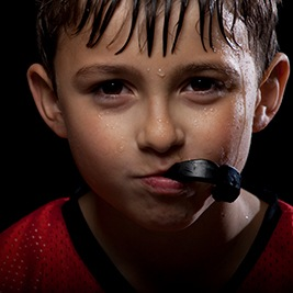 Boy with black mouthguard in mouth