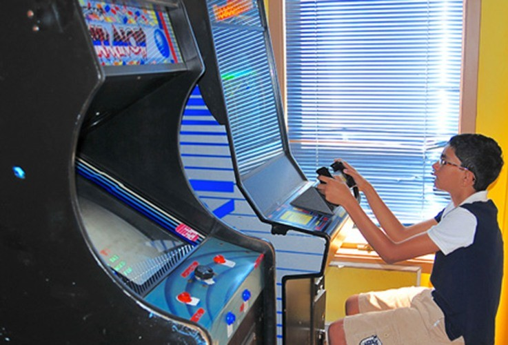 Child playing arcade games in waiting area