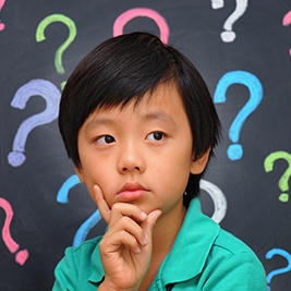 Little boy with question marks around his head