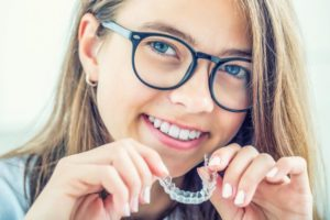 Girl smiling with Invisalign tray