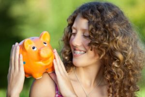 teenager holding a piggy bank for braces