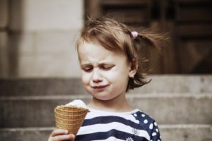 Frowning child with tooth sensitivity holding an ice cream cone