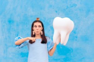 Tooth Fairy making a silly face and pointing to model tooth