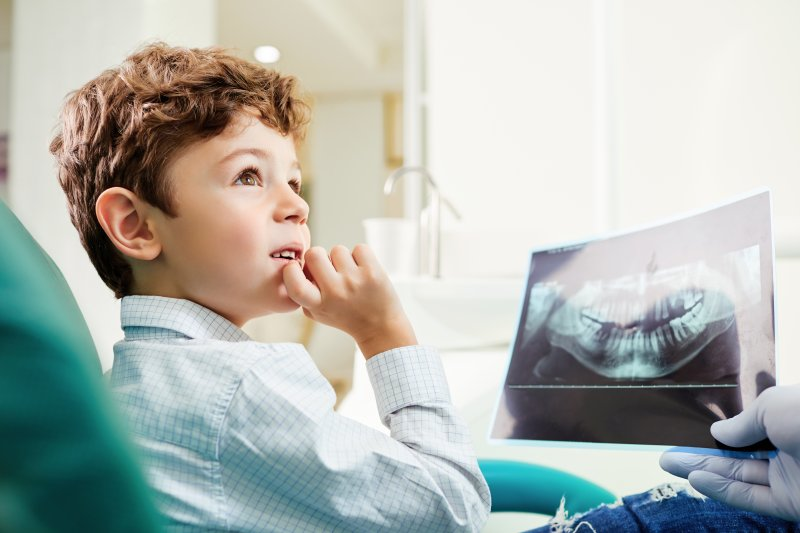Child looking at X-ray in dentist's chair